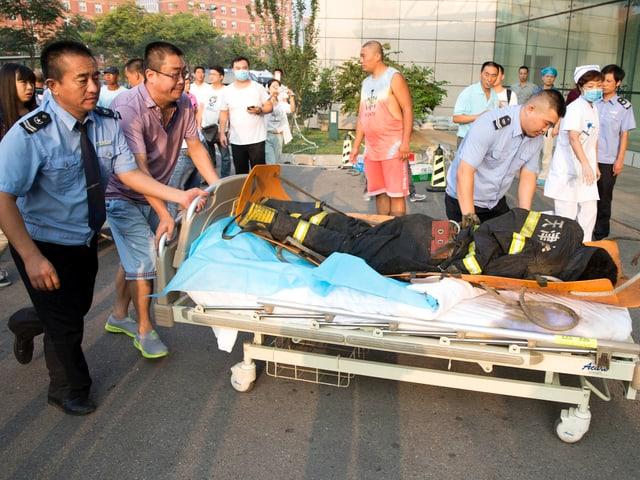 Ein Feuerwehrmann wird von Helfern auf einer Trage geschoben.