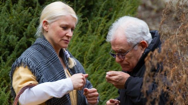 Eine blonde Frau mit schwarzen Schal zeigt älterem Herr Kräuter im Garten