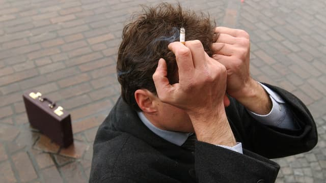 In um cun ina cigaretta en maun che tegn ils mauns avon il chau.