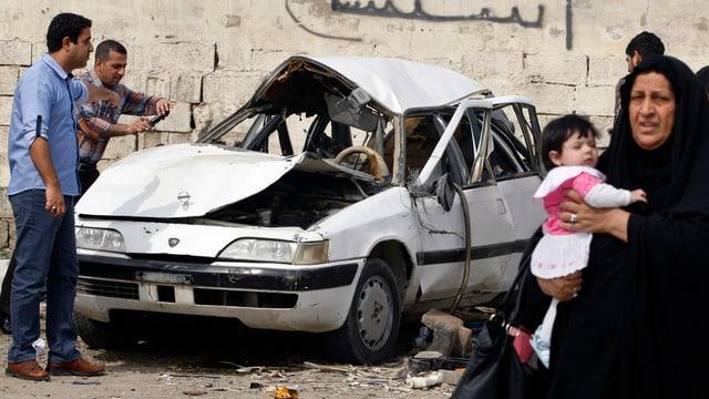 Explodiertes weisses Auto, daneben einige Menschen.