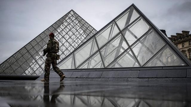 Soldat vor den Glaspyramiden, die vor dem Louver stehen.