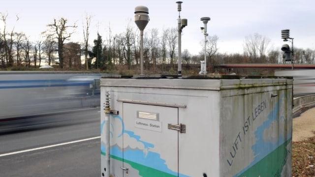 Messstation mit Messinstrumenten auf dem Dach. Im Hintergrund Autobahn