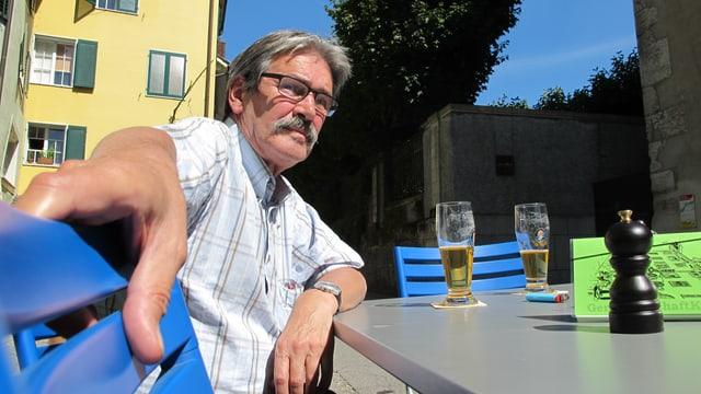 Zanetti sitzt vor einer Stange Bier an einem Tisch des Restaurants.