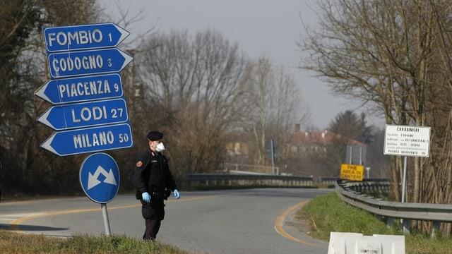 Carabinieri steht an Strassenkreuzung mit Schildern.