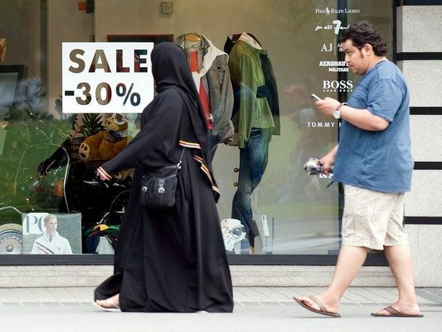 Ein arabisches Ehepaar, die Frau verschleiert, vor einer Interlakner Boutique