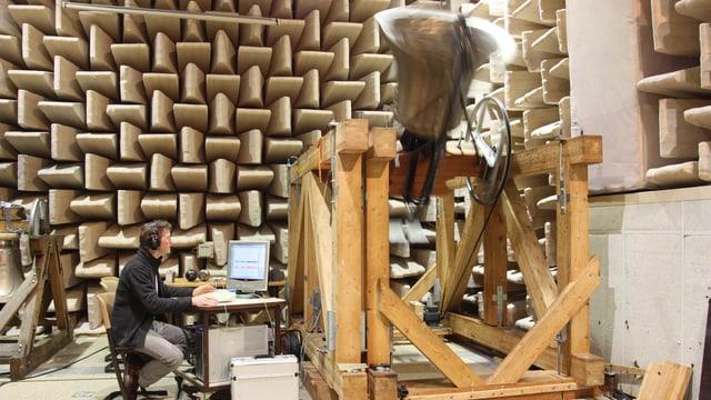Ein grosse Glocke ist an einer Holzkonstruktion befestigt und schwingt weit nach oben. Davor sitzt ein Mann an einem Computer. Im Hintergrund an der Wand sind Schallschutzelemente befestigt.