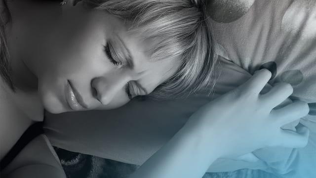 Frau liegt mit geschlossenen Augen im Bett und wird blau beleuchtet