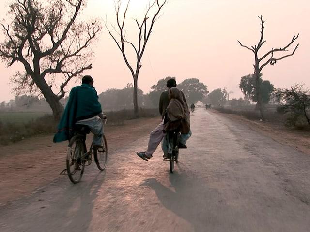 Zwei Männer fahren auf Fahrrädern auf einem ungeteerten Weg in der Morgensonne.