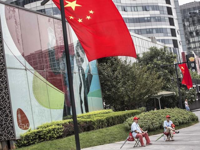 Zwei Personen sitzen unter chinesischer Fahne.