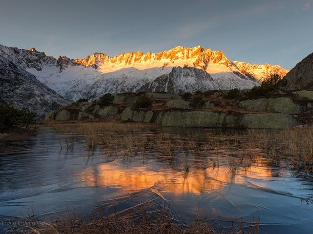 Im Vordergrund ein gefrorener See, dahinter eine Bergkette, die von der Sonne beleuchtet wird.