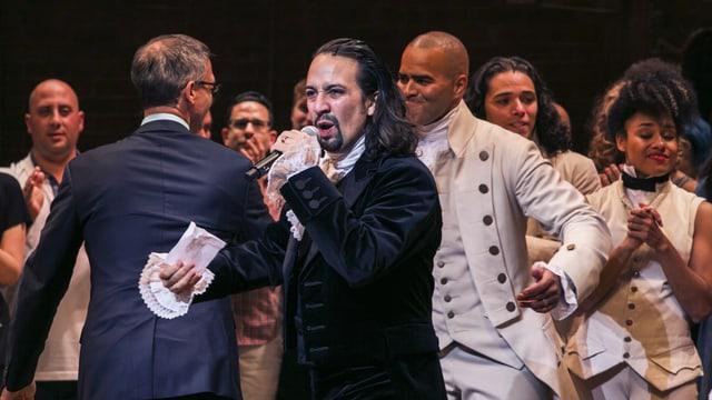 Lin-Manuel Miranda als Hamilton mit Mikrophon auf der Bühne, um ihn weitere Musicaldarsteller und -darstellerinnen in historischen Kostümen.