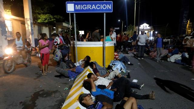 Personen, die vor einem Grenzposten sitzen.