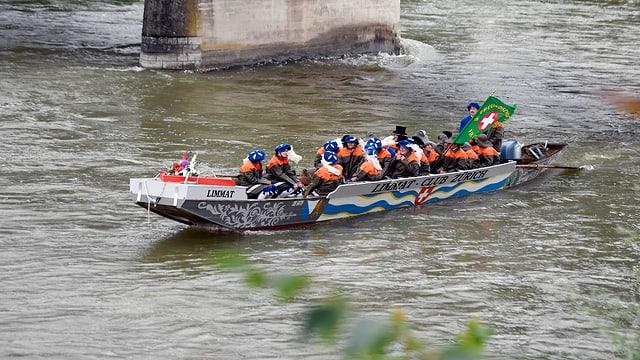 Ein Langboot, drinnen sitzen blau-uniformierte Zunftmitglieder.