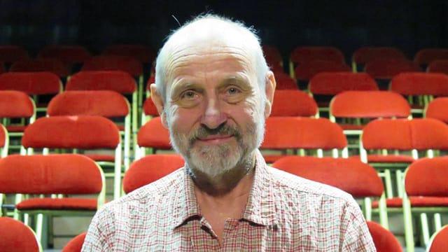 Peter Freiburghaus vor roten Stühlen.