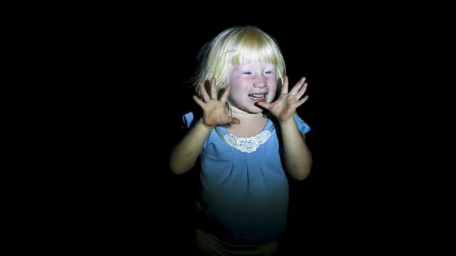 Ein hellblondes Kind steht im Dunkeln und wird angeleuchtet, es hält die Hände mit gespreizten Fingern in die Höhe.