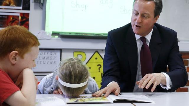 Englands Premier David Cameron sitzt an einem Schultisch, zusammen mit einem kleinen Jungen und einem Mädchen. Das Mädchen hat seinen Kopf mit dem Gesicht nach unten auf den Tisch gelegt.