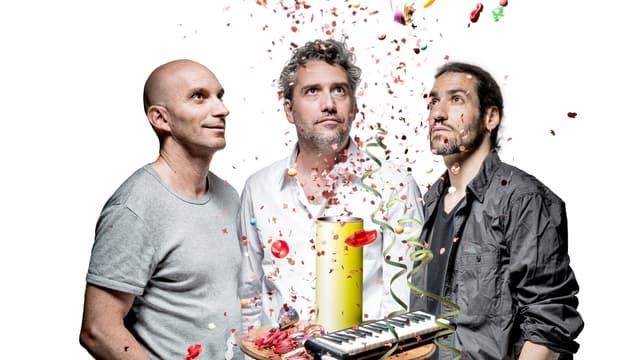 Drei Männer bestaunen eine eben geplatzte Tischbombe.