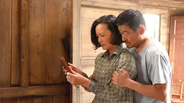 Halbtotale von der Seite: Eine Frau betrachtet ein Bild, hinter ihr steht ein Mann, der sie von hinten umarmt. Die beiden machen ein trauriges Gesicht.