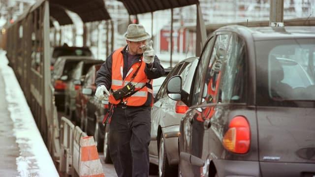 Mann weist Autos beim Autoverlad ein.