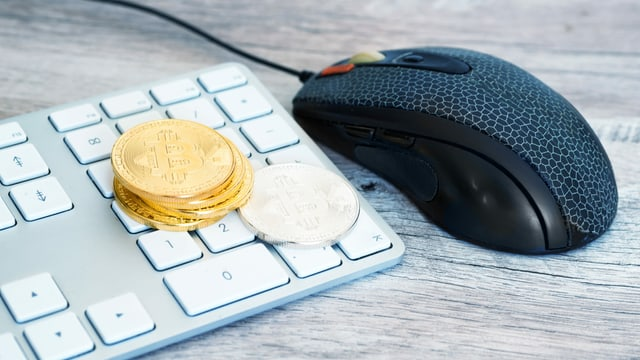 Symbolbild: Tastatur mit goldenen Bitcoin Münzen