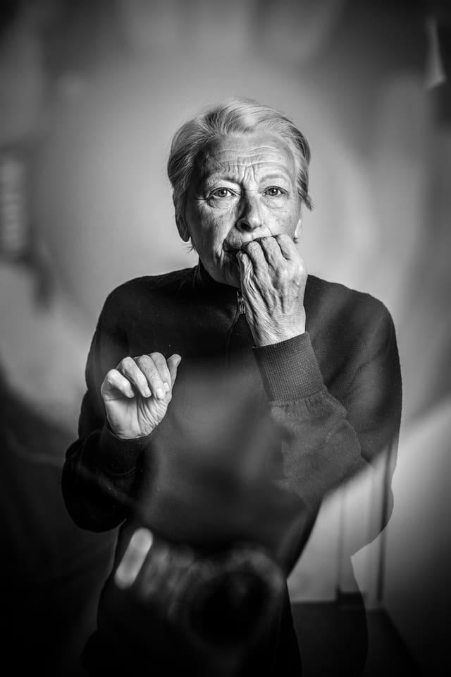 Portrait einer älteren Frau, die die Finger einer Hand im Mund hat. Im Bild ist auch der Schatten des Fotografen zu erkennen.