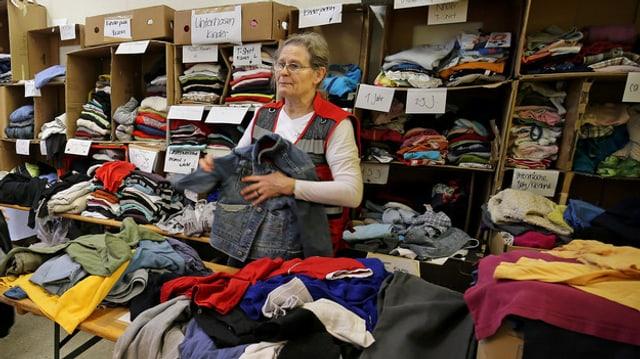 Eine Frau inmitten von Kleidern