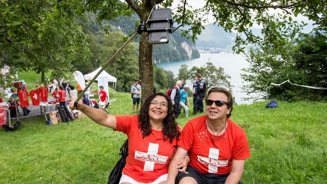 Eine Frau und ein Mann in rot-weissen Schweizershirts machen ein Selfie.