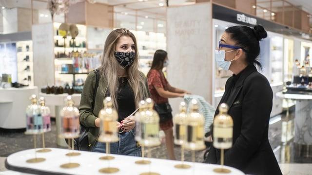 Eine Frau mit Atemschutzmaske testet Düfte, aufgenommen im Warenhaus Jelmoli in Zürich.