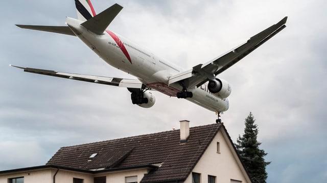 Ein Flugzeug überfliegt knapp die Dächer eines Wohngebietes in Kloten