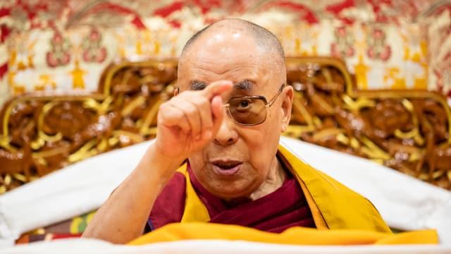 Der Dalai Lama deutet mit dem Zeigefinger in die Luft.