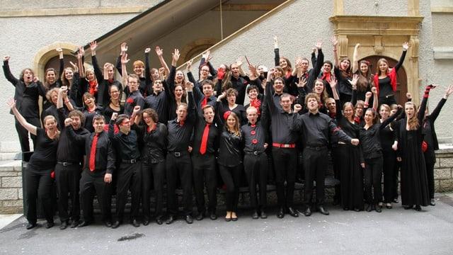 Eine Gruppe von jungen Frauen und Männern, schwarz bekleidet und mit roten Accessoires, vor der Treppe eines alten Gebäudes.