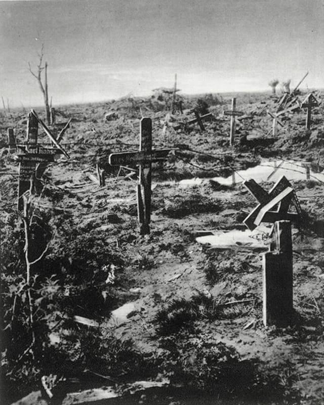 Feld mit zerstörten Grabkreuzen aus Holz.