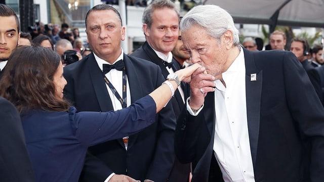 Alain Delon küsst die Hand einer Frau auf dem roten Teppich in Cannes.