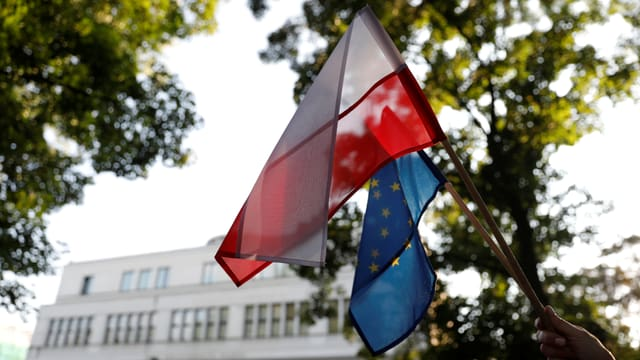 Polnische und EU-Fahne nebeneinander, Gebäude im Hintergrund.