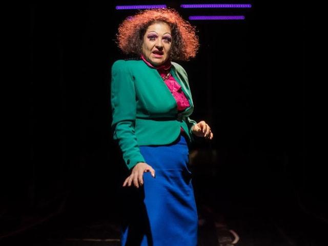 Eine Frau mit verstruwelter Frisur und knalligen Kleidern steht auf der Bühne.