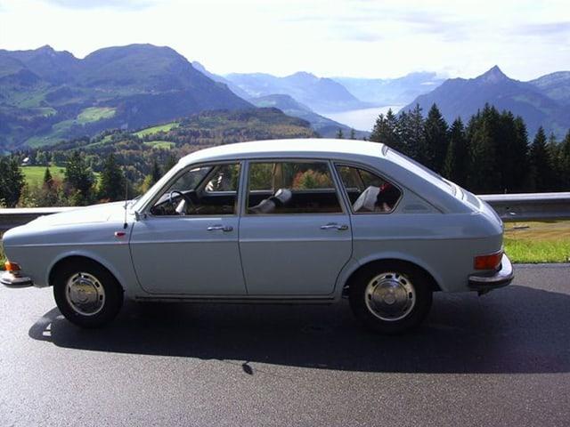 Ein älterer aber noch fitter Wagen auf einer Bergstrasse.