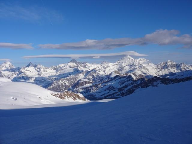Verschneite Bergwelt, blauer Himmel. Über dem Gipfel eine Wolke, die wie ein Haufisch aussieht