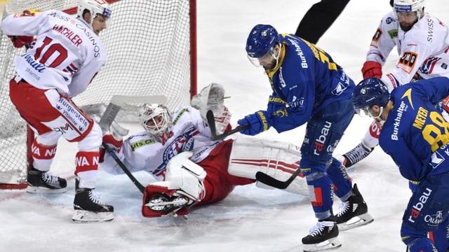 Giugader dal HCD emprova da sajettar in gol. Goalie en dies, auter hockeyan adversari dal HCD er.