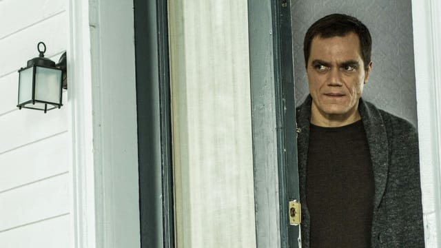 Michael Shannon schaut kritisch. Er steht an einer halb-offenen Tür.
