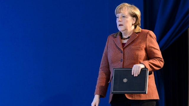 Angela Merkel mit schriftlichen Unterlagen in der Hand am WEF in Davos.