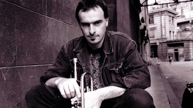 Mann mit Trompete kauert auf einer Strasse.