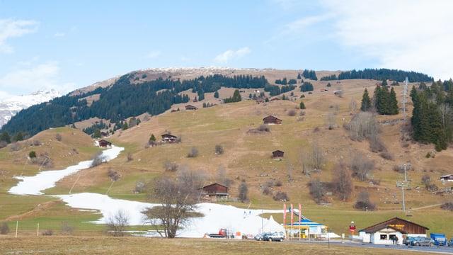 Il territori da skis sur Breil cun spundas verd-brinas ed ina sdrima da naiv.