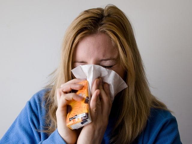 Eine Frau niest