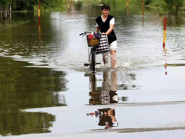 Eine Frau schiebt ihr Fahrrad durch knietiefes Wasser.