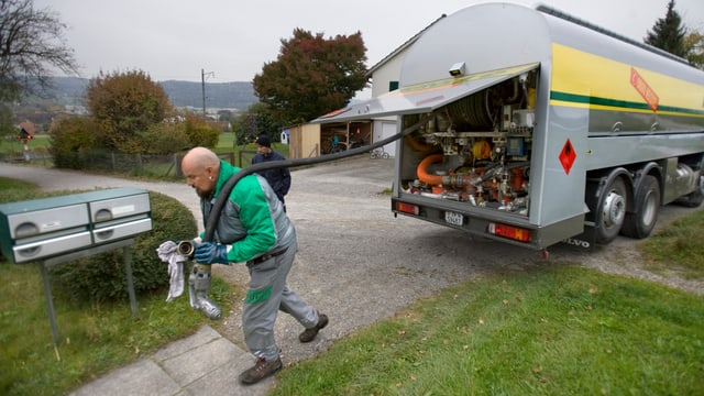Mann zieht Schlauch aus Lastwagen zu Haus hin, um Heizöl in die Heizung zu pumpen.