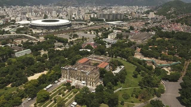 Luftaufnahme des zerstörten Museumsgebäudes. Im Hintergrund ein modernes Fussballstadion