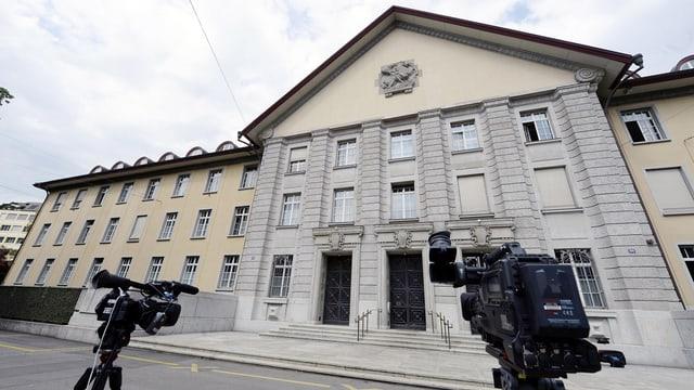 Die Fassade des Bezirksgebäudes in Zürich, im Vordergrund zwei Fernsehkameras auf Stativen.