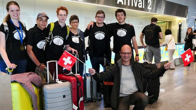 Fünf Schüler mit Digitalredaktor Reto Widmer, der zwei Schweizerfähnchen hält.