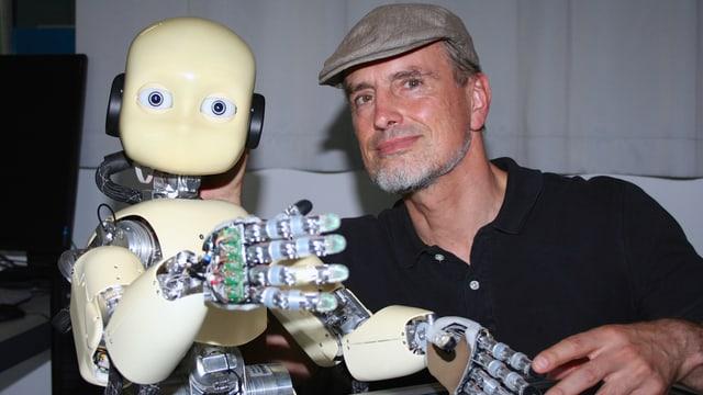 Schmidhuber posiert mit einem Roboter mit niedlichen, kindlichen Gesichtszügen.