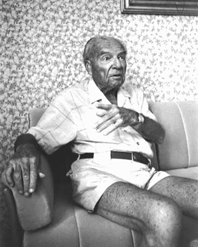 Mann sitzt auf einem Sofa vor einer Blumentapete.